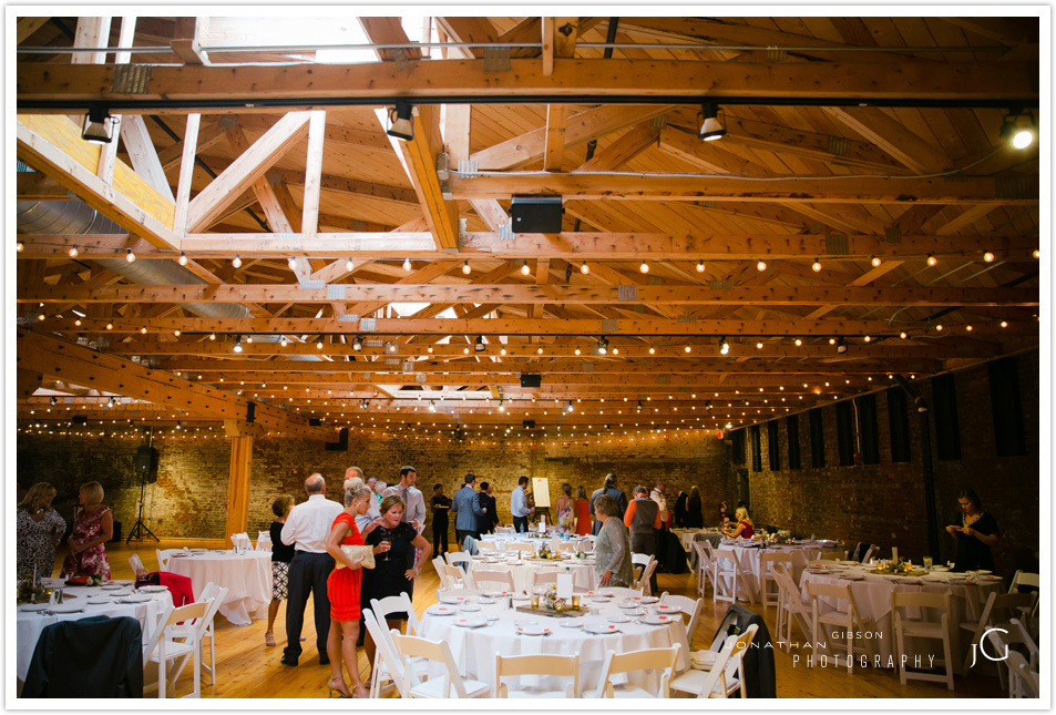 Liz + Andy's beautiful Cincinnati wedding reception at Rhinegeist Brewery. Tables were set with gilt geometric vessels filled with small wildflowers + votives on rustic boards. Watercolor table numbers by the brides best friend. Floral design by Yellow Canary located in the Cincinnati and Northern Kentucky area. www.yellowcanaryonline.com
