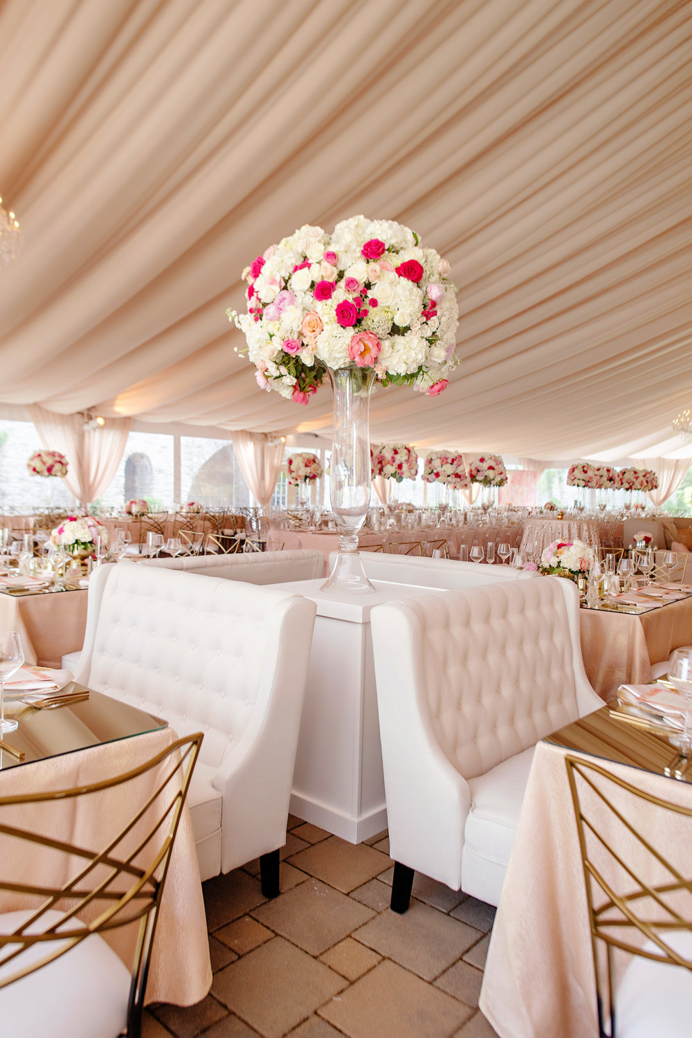 Outdoor tented reception with chandeliers and large focal arrangements in blush, magenta, and white by Yellow Canary Floral Design