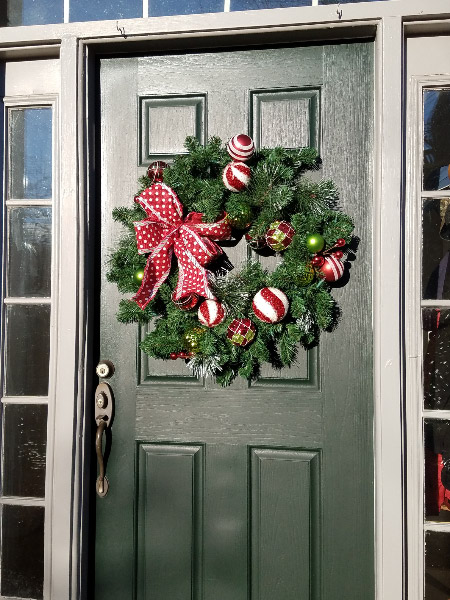 - My husband decided we needed something festive on the door – so he bought a wreath with battery powered LED lights. I like it best during the daytime and it does provide a festive look on the door.