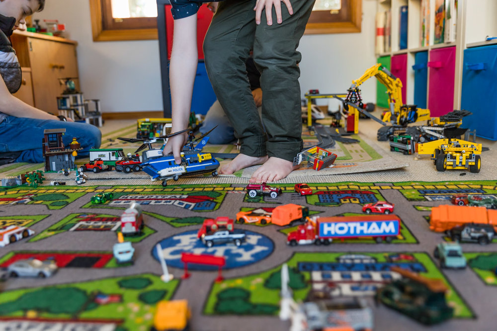 a boy reaching down to pick up a Lego police helicopter off a play mat