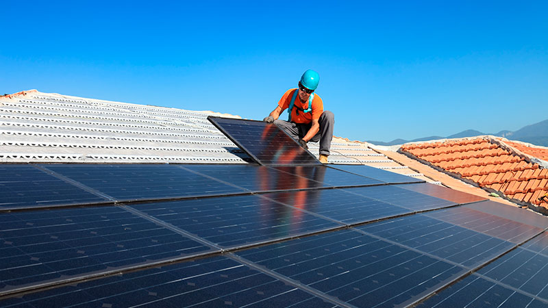 man-installing-solar-panels-on-roof.jpg