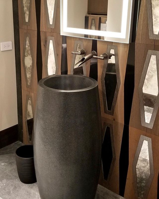 This black marble pedestal sink is accented by contrasting wood tiles inlaid with weathered diamond shaped mirrors and a lighted vanity mirror for a unique look thats both chic and rustic, perfect for our modern mountain home. #solannadesign
