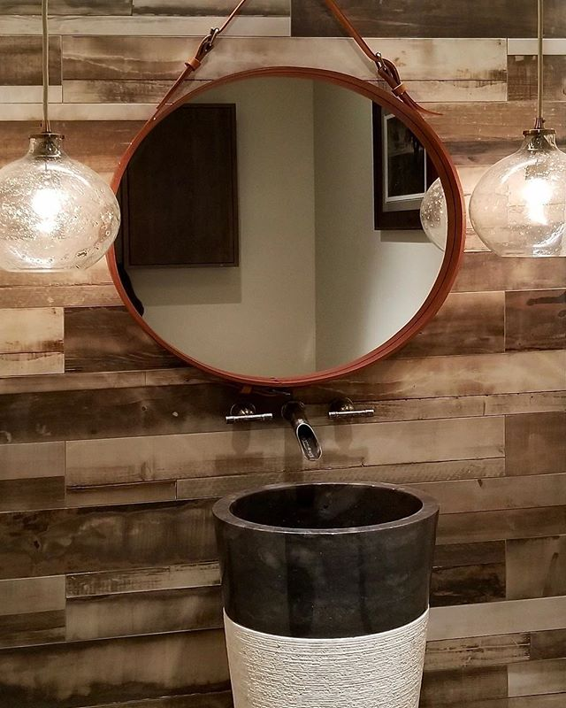 Suspended from a natural leather strap with detailed brass hardware, this round looking glass is set deep within a leather wrapped brass frame and highlighted by two decorative sand-infused glass pendant lights for a chic yet rustic look unique to #solannadesign