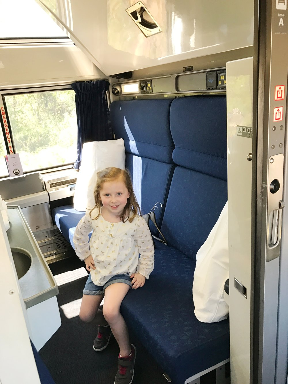 Mattie Grace modeling a room on the Amtrak train - everything folds out to make two bunk beds!