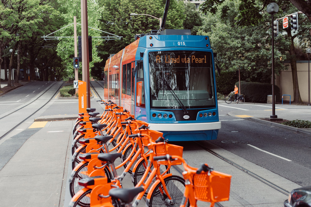 [Photo: The Portland Streetcar passes a BIKETOWN bike-share docking station. Credit: TriMet.]