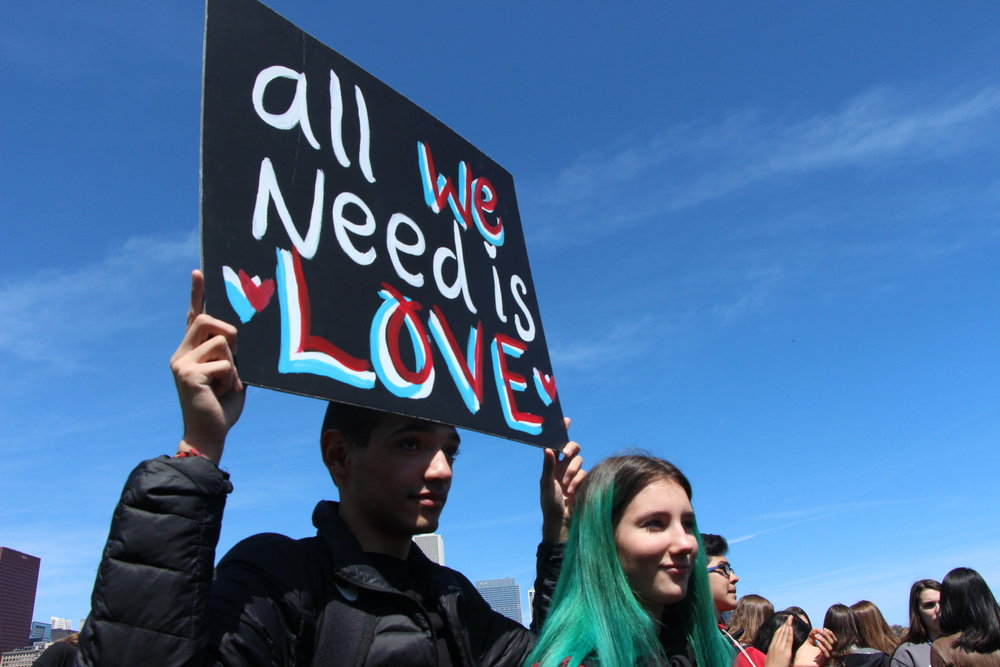 Student signs plead for their lives, urging for gun control so that we put down the guns and spread the love.