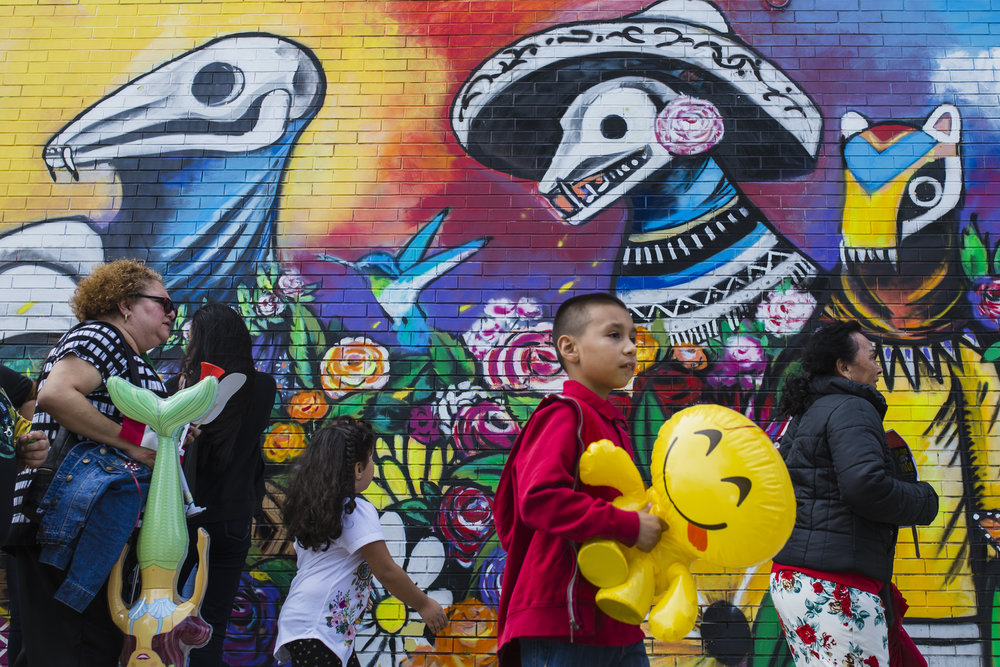 Spectators at the Mexican Independence Day Parade pass by a mural in the colorful Little Village neighborhood.