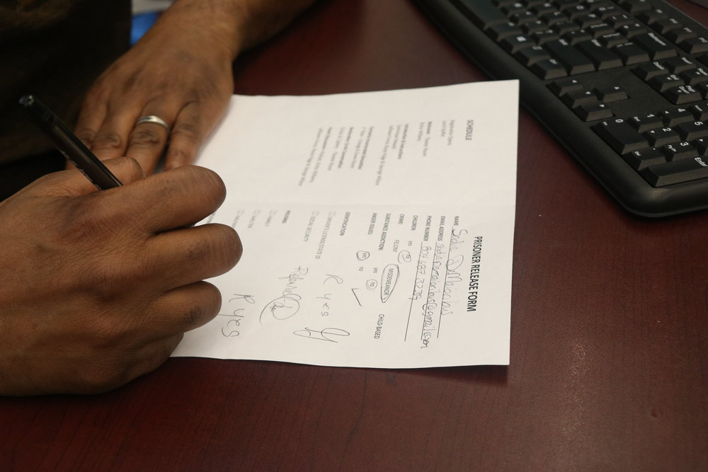 George Wilson fills out a form for one of the participants who is acting as a re-entering individual in need of employment.
