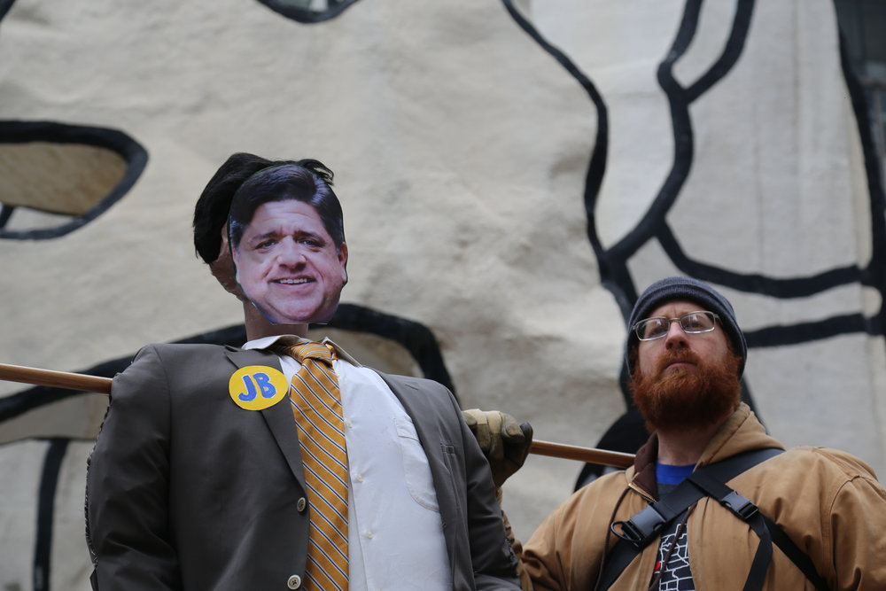 A man holds up a cardboard cut-out puppet of Gov. J.B. Pritzker