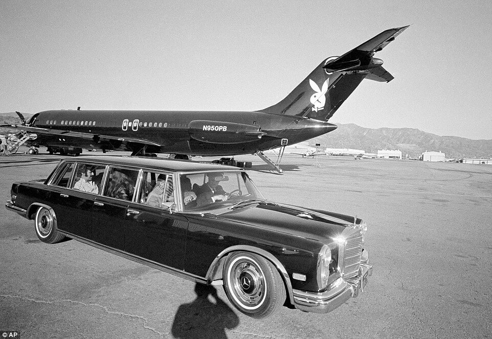 Hugh Hefner leaves the comfort of his private jet in his Mercedes Benz 600 limousine with the Bunnies in tow
