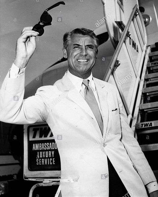 Cary Grant waves as he boards a TWA flight