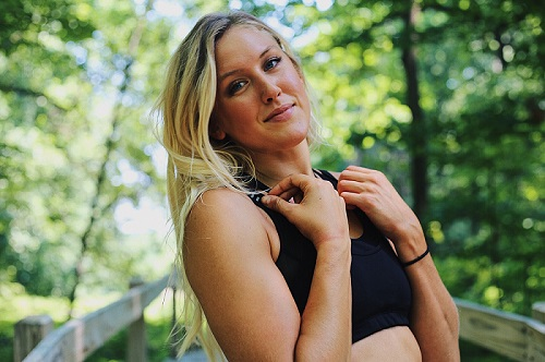 Blonde fitness girl smiling outside in the forest.