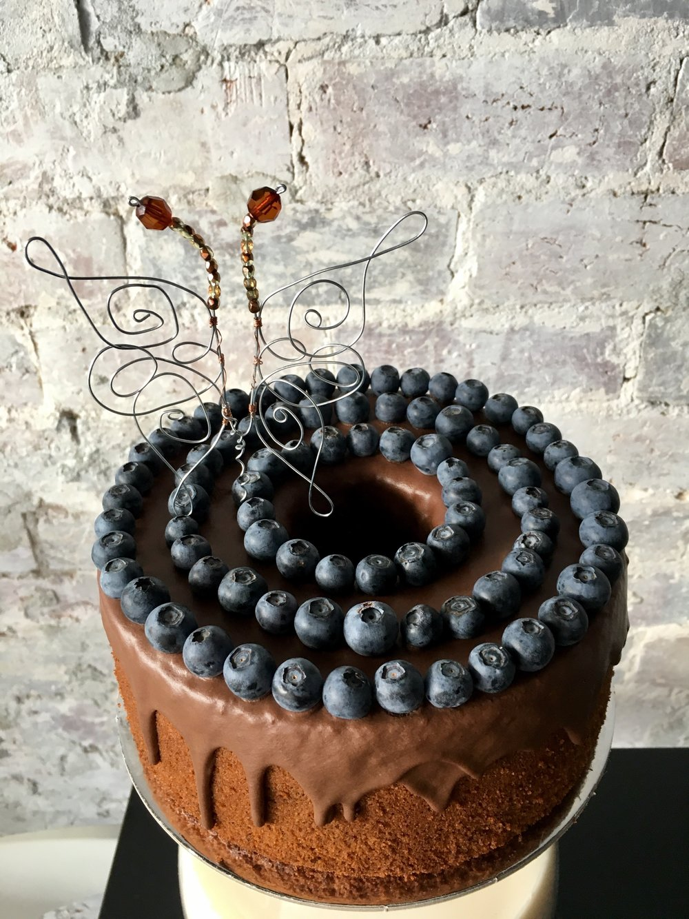 Blueberry Chocolate - Light as air chocolate chiffon cake, with velvety chocolate ganache and fresh blueberry detail.Wire butterfly made in-house.