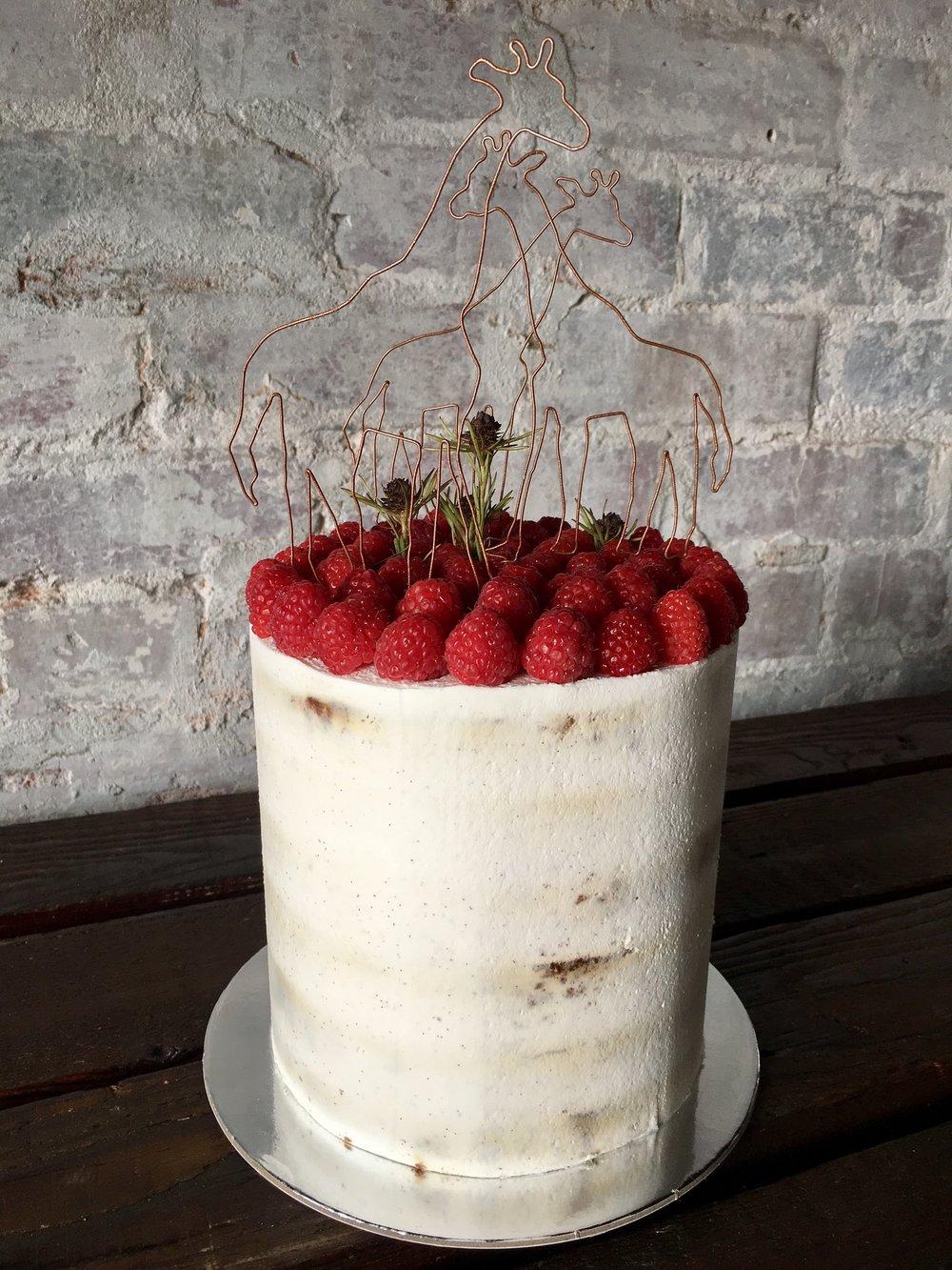 Hazelnut Raspberry - Hazelnut and chocolate truffle cake, with vegan coconut creme, fresh raspberries and floral arrangement. Semi naked exterior. In house made wire giraffe.