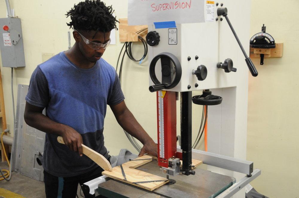 Co-head of Engineering Hezekiah Carlisle Cutting the Base of the robot