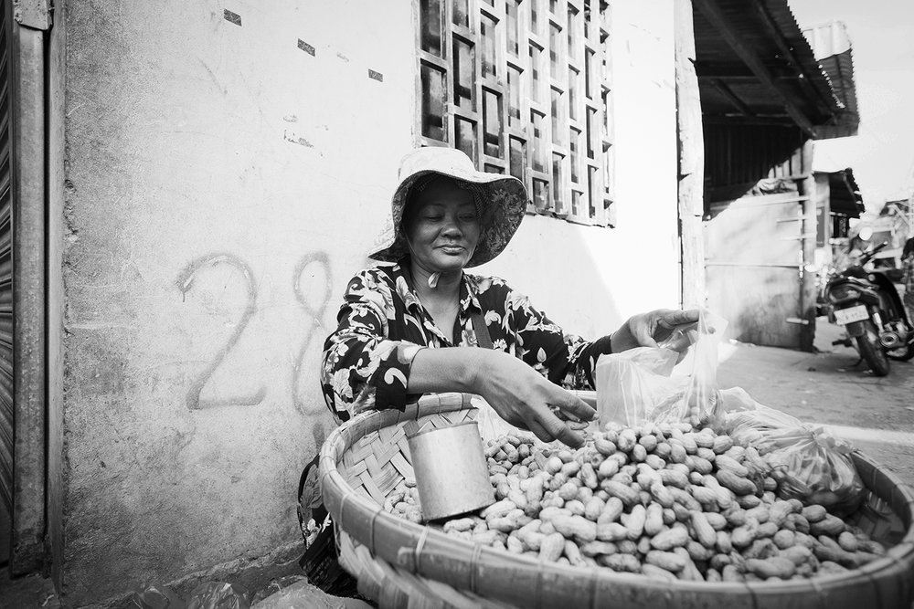 A woman selling peanuts on the dry side of the street.