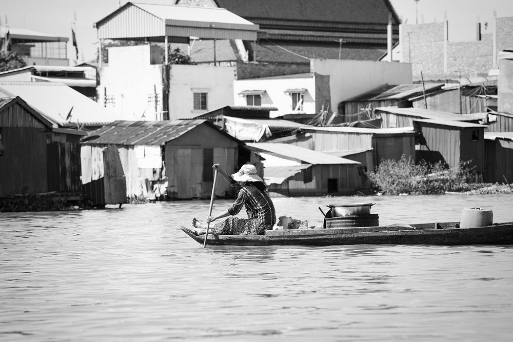 A woman returning home after spending the morning selling food from her boat.