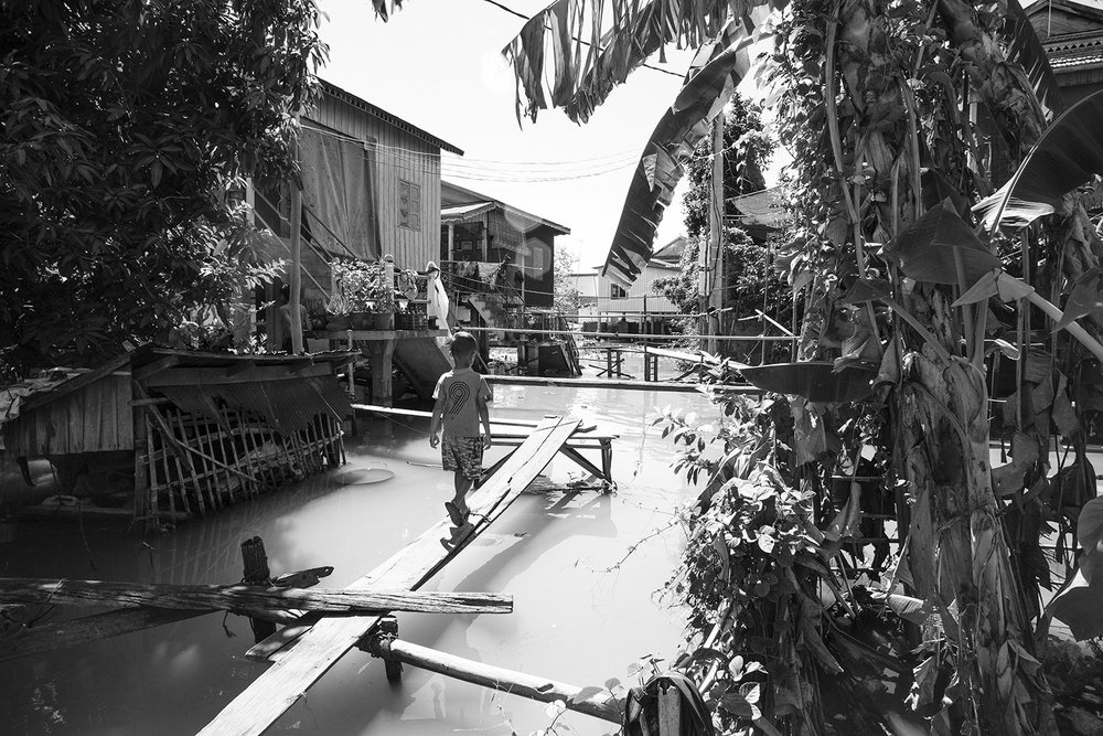 A child walking to his home behind the Asian Hope school, located to the right, behind the banana trees.
