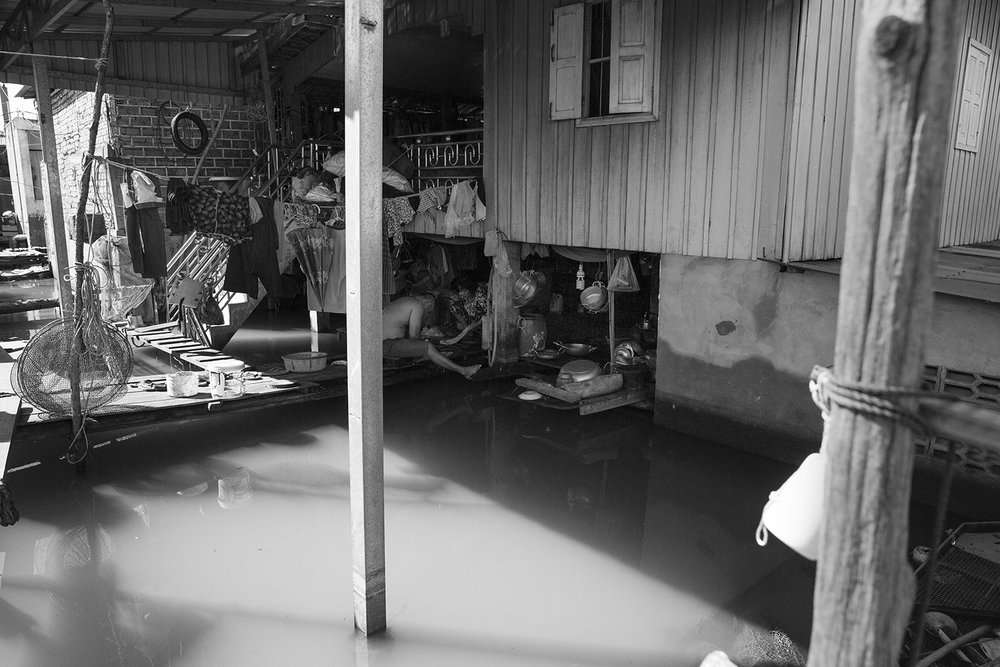 An elderly couple preparing food in the flooded first floor of their stilt home. The water is approximately 9 feet deep here.