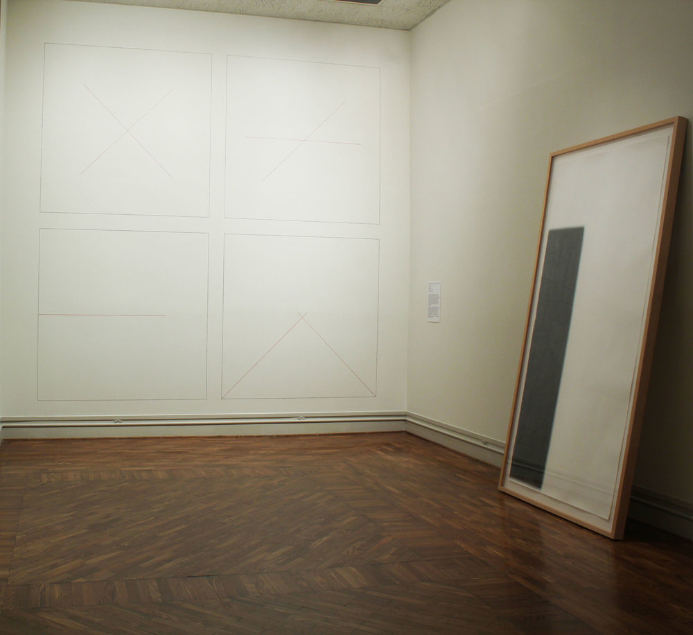 "Beyond the Grid/ Into the Sublime, A New View on Minimalism (installation view, 2014)  Susan York, Tilted Column (right), 2008, graphite pencil on paper, 8' x 4' x 2"" (framed)  Sol LeWitt,  Wall Drawing series (left)"