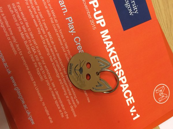A keyring in the shape of a cat's face displayed on the orange Makerspace leaflets