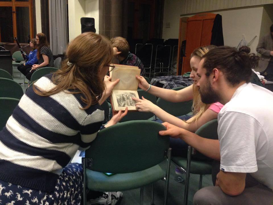 Three people examining an old printed copy of  The Mystery of Edwin Drood .