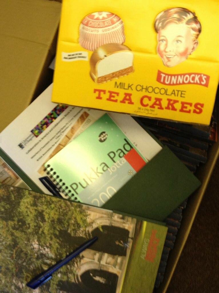A UofG branded conference pack with a notebook and a large box of Tunnocks Tea Cakes