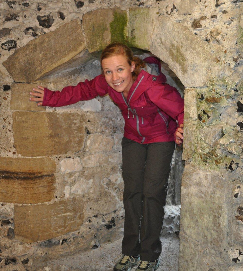 Sapphire Wanmer climbing through a thick stone portal