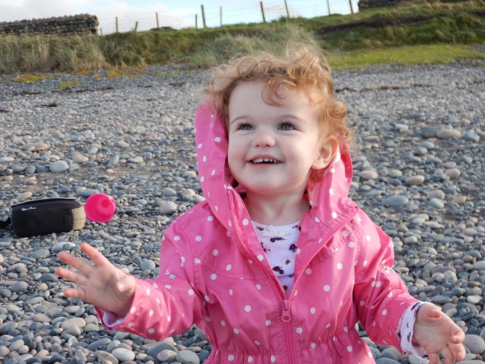 A child wearing a spotted pink cloak on a pebble beach
