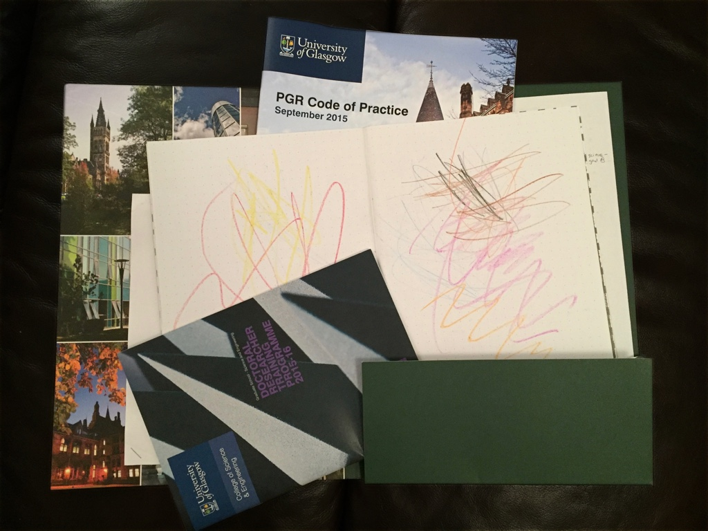An image showing some University of Glasgow stationary, along with some children's drawings.