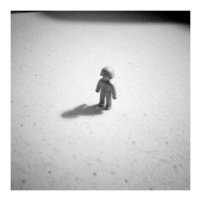 A black and white image of a small toy figure standing alone on what appears to be a kitchen worktop / desk.