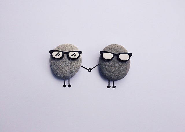 Rock, Craft, People, Friends, Support. An image of two pebbles with cartoon sunglasses, arms and legs. They are holding hands.