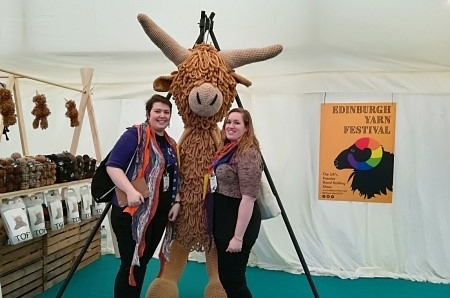 Tipsy Knits podcasters Cia and Pip and Edinburgh Yarn festival next to a large crafted Highland Cow