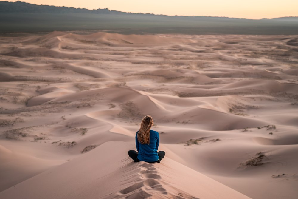 Woman sitting with the legs crossed on the sand contemplating the horizon
