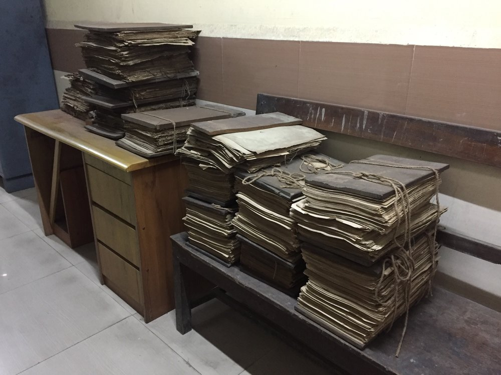 [Image description: Stacks of documents from an archive in India lying on top of a desk and bench.]