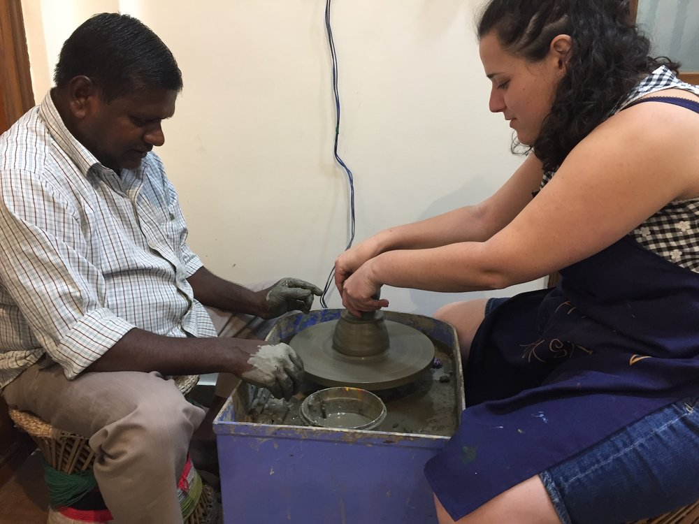 [Image description: Lydia and a man from India working on a piece of pottery together at a pottery wheel.]