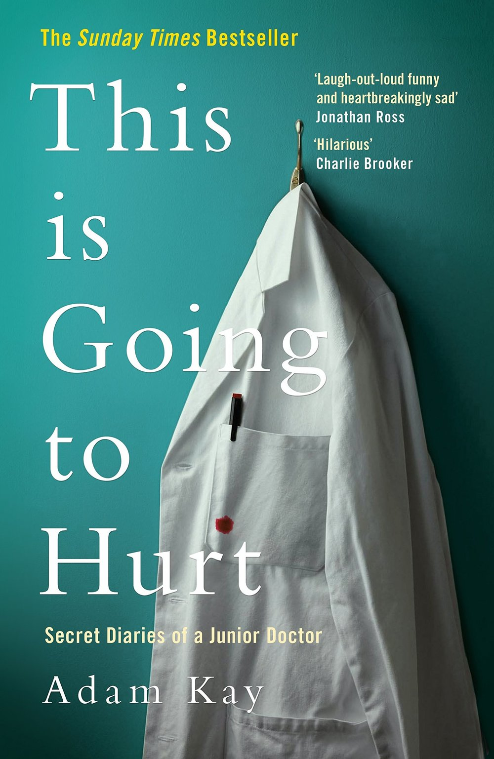 Front book cover of 'This is Going to Hurt: Secret Diaries of a Junior Doctor' by Adam Kay. The image displays a white lab coat hung up on a hook against a teal coloured wall. There is pen placed in the breast pocket of the coat, and a spot of blood on the pocket of the lab coat.