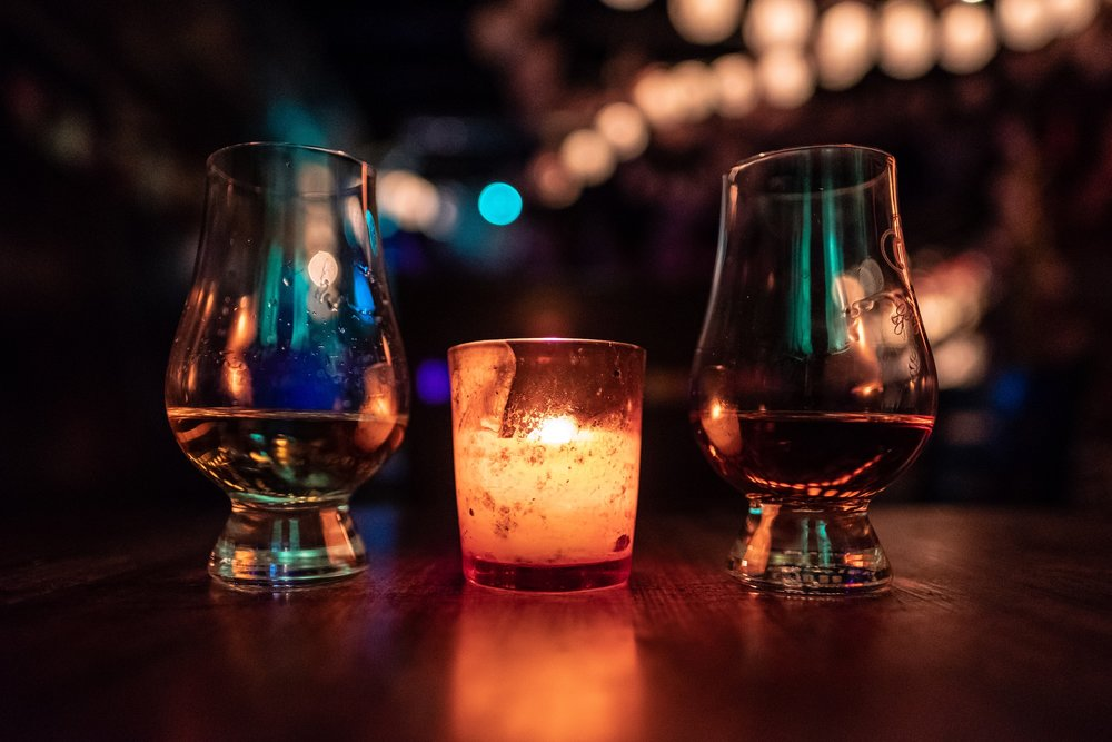 [Image description: A small burning candle sit in between two dram glasses filled with whisky.]