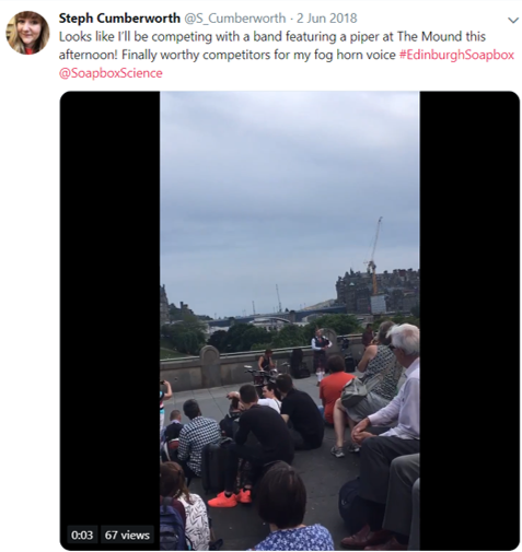 Screenshot of a tweet by Stephanie (@S_Cumberworth) which says 'Looks like I'll be competing with a band featuring a piper at The Mound this afternoon! Finally worthy competitors for my fog horn voice #EdinburghSoapbox @SoapbocScience.' There is a still from a video of a crowd gathered in Edinburgh around a band and a man playing bagpipes.