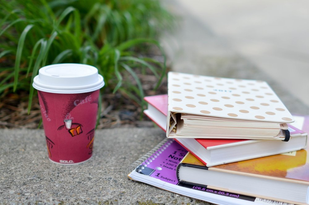 [Image description: A take-away cup sitting next to a pile of books in front of grass.]