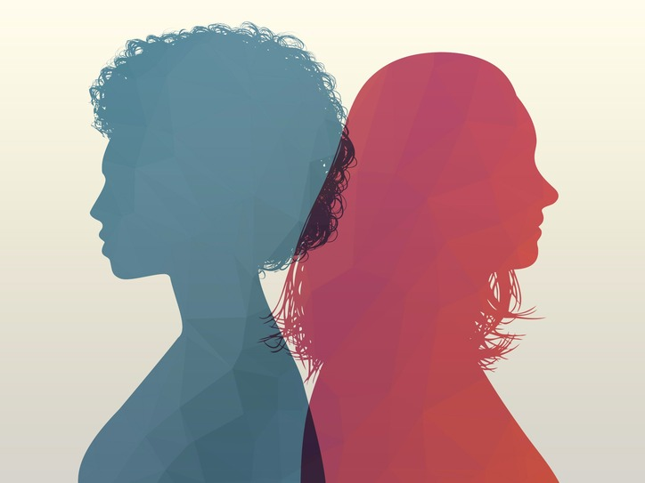 [Image description: A silhouette of two women from different backgrounds standing back to back]
