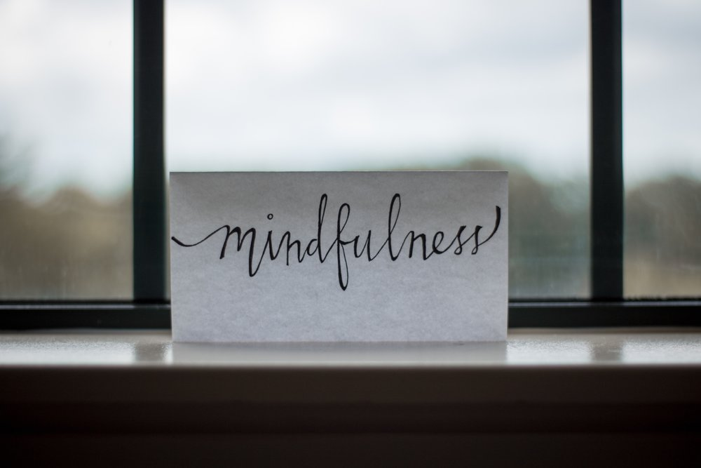 [Image description: 'Mindfulness' is written in cursive on a piece of white paper that is propped on a windowsill.]