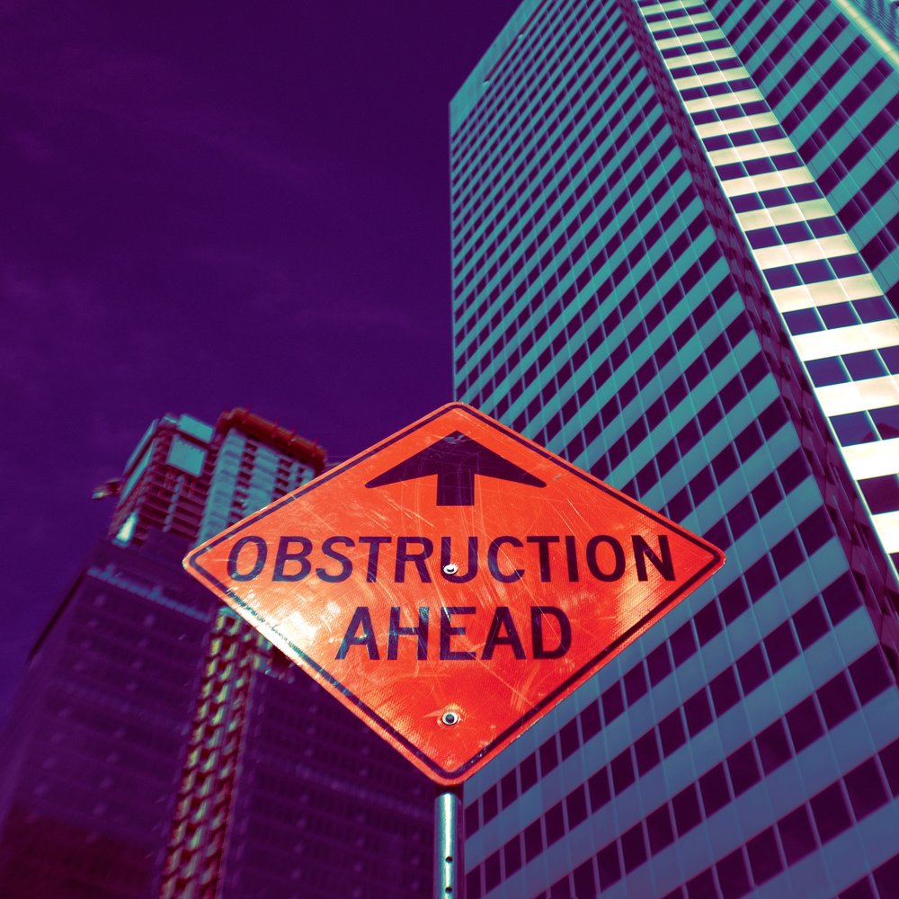[Image description: An orange traffic sign that has an arrow pointing up and says 'OBSTRUCTION AHEAD' sits amongst skyscraper buildings in a city.]