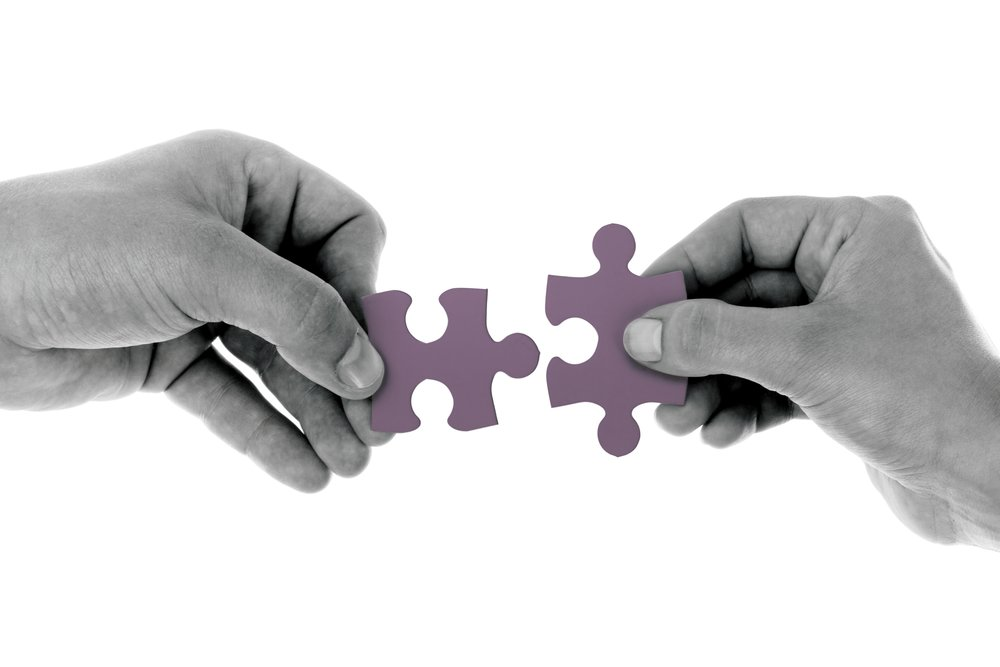 Two hands holding separate pieces of a puzzle