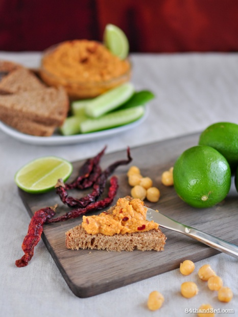 Smokey Chilli & Lime Hummus Serves 12    The round warm spiciness of dried chillies combined with smokey tahini and sour lime juice makes for a stunning twist on classic hummus.     INGREDIENTS:    · 2 can chickpeas, drained and rinsed  · 5-6 dried chilies, soaked in 1/2 c boiling water (or to taste)  · 2 garlic cloves, peeled  · 6 Tbsp olive oil  · 2 Tbsp tahini  · juice from 2 limes, approx 1 – 2 Tbsp  · big pinch sea salt  · 4 tsp sweet smoked paprika   To serve   · chili flakes, lime wedges, olive oil    METHOD:    Pour boiling water over chillies, set aside to soften 10 mins. Drain and reserve soaking water, remove stems from chillies. Puree all ingredients, adding a bit of the chili soaking water to make a smoother puree if necessary.