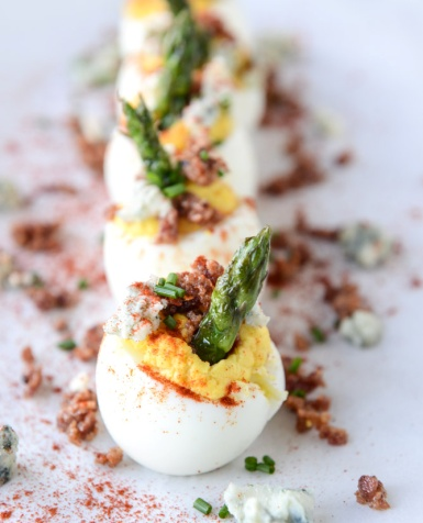 BACON BLUE DEVILED EGGS WITH ROASTED GARLIC AND ASPARAGUS    yield:  MAKES 18 DEVILED EGGS    total time:  2 HOURS (A LOT OF DOWN TIME)  INGREDIENTS:  2 heads garlic 18 large eggs 10 slices thick-cut bacon 10 asparagus spears, woody stems removed 1 pinch each of salt, pepper and garlic powder  1/2 cup mayonnaise 1/4 cup plain greek yogurt (full fat!) 1 1/2 tablespoons dijon mustard 1/4 teaspoon salt 1/4 teaspoon pepper  2 ounces blue cheese, crumbled 1/2 teaspoon smoked paprika 2 tablespoons fresh chives  DIRECTIONS:  Preheat the oven to 350 degrees F. Slice the top off the heads of garlic and drizzle them with olive oil. Wrap them tightly in aluminium foil and place it in the oven to roast for 45 to 60 minutes. You want the cloves to be caramely and golden. Remove the garlic and unwrap it, allowing it to cool until you can touch it. You can do this a day or two ahead of time if you'd like!  To boil the perfect egg, place the eggs in a large pot and fill it with cold water. Bring it to a boil and let bubble for 1 minute, then turn off the heat and cover the pot. Let the pot sit for 15 minutes. After 15 minutes, place the pot in the sink and fill it with cold water to cool the eggs down immediately. You want the eggs to sit in cold water for 30 minutes or so, so you will need to dump the water and refill with cold water a few times. You can add some ice cubes too!      BACON BLUE DEVILED EGGS WITH ROASTED GARLIC AND ASPARAGUS (cont.)  While the eggs are cooling, heat a large skillet over medium-low heat and cook the bacon until crisp and all the fat is rendered. Place the bacon on a paper towel to drain the grease. Keep 1 to 2 tablespoons of the grease in the skillet (reserve the rest!) and throw the asparagus in the skillet. Sprinkle it with salt, pepper and garlic powder. Cook for 5 minutes, just until slightly softened. Turn off the heat.  After 30 minutes, peel the eggs and place them on a paper towel. Slice off a TINY piece of the fat bottom of the egg so it can