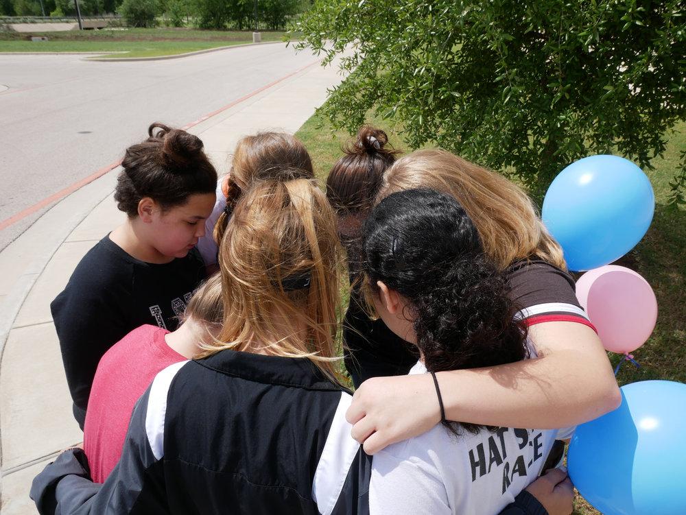 Girls praying together before releasing balloons.