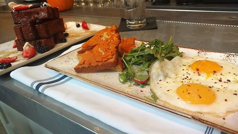 Gluten-free brunch indulgence from The Little Beet Table featuring French Toast with fresh berries and crème fraiche, sweet potato toast, over-easy eggs and greens.
