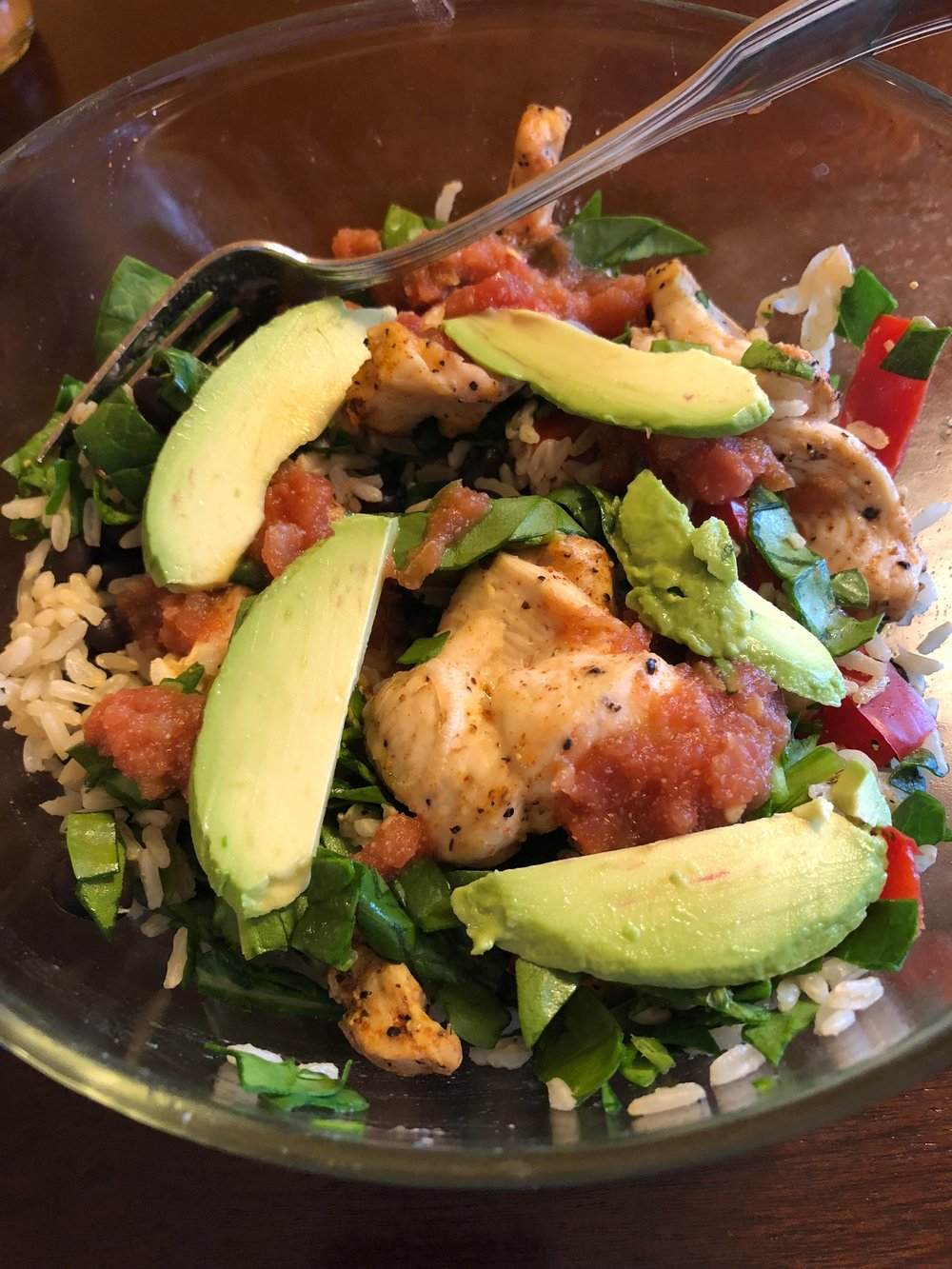 Chicken fajita bowl with brown rice, chopped spinach, avocado and black beans.