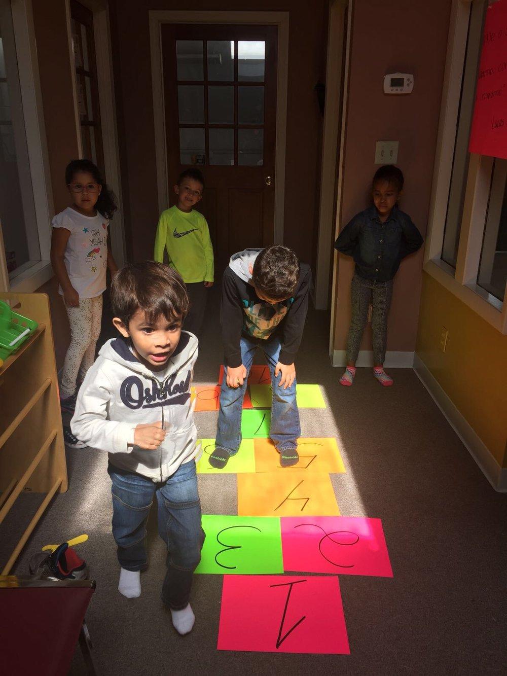 Alunos brincando de amarelinha como uma maneira de praticar a língua Portuguesa durante a nossa aula do programa Plus Português.